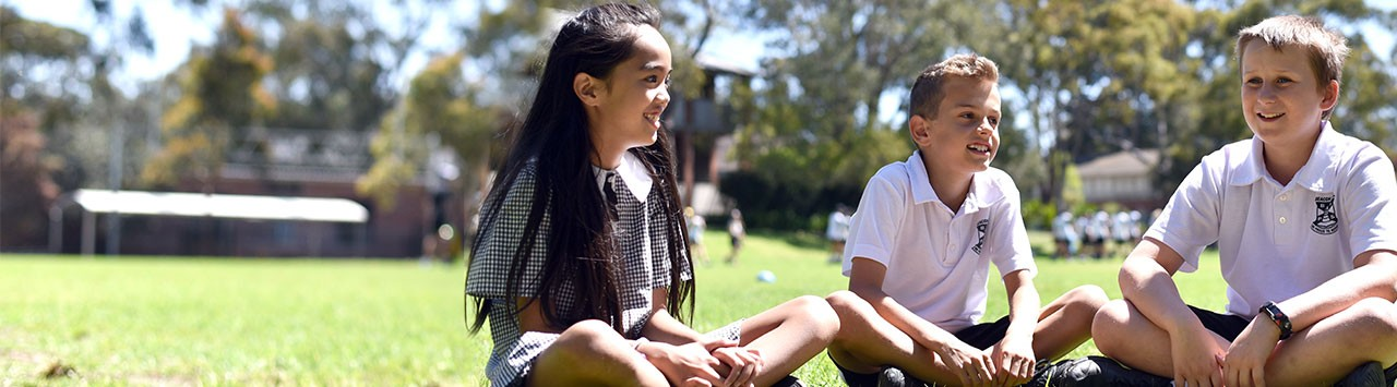 Students sitting on the grass and smiling.